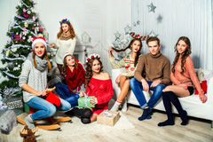 La società di sei ragazze e tipi vicino all'albero di Natale Immagini Stock Libere da Diritti