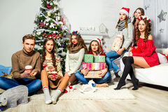 La società di sei ragazze e tipi vicino all'albero di Natale Fotografie Stock