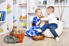 La soeur joue avec son frère des vacances de Pâques image libre de droits