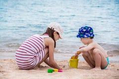 La soeur plus âgée et le jeune frère construisent du sable sur le bord de la mer Image stock