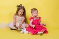 La soeur plus jeune pleure, l'aîné garde le téléphone sur le fond jaune Photographie stock