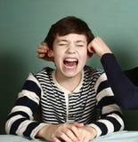 La soeur tirent ses oreilles de garçon de frère en raison du pari Photographie stock libre de droits
