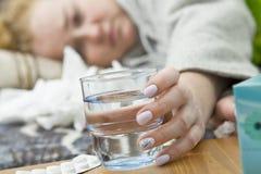 La sofferenza della giovane donna dall'emicrania, dal freddo e dall'influenza sta tenendo un g immagini stock