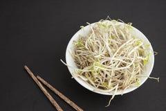La soia germoglia in ciotola e bastoni di legno cinesi Immagini Stock