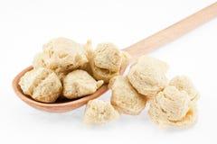 La soia si sfalda in cucchiaio di legno su priorità bassa bianca Immagine Stock Libera da Diritti