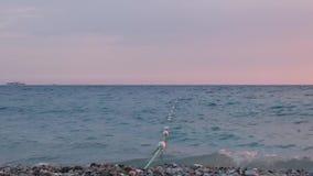 La soirée d'été vagues de côte à de petites surfent sur les cailloux gris banque de vidéos