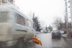 La soirée, pluie chute sur la fenêtre avec la tache floue du trafic Silhouette trouble de voiture Autumn Abstract Backdrop Image libre de droits