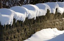 La sol y el casquillo de la nieve fresca definen una pared de piedra Fotos de archivo