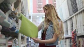 La sola mujer joven está tomando de estante en una tienda un rollo del wallcovering metrajes