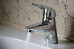 La sola palanca cromó el mezclador con la agua corriente en el cuarto de baño, w fotografía de archivo