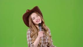 La solista canta le canzoni di paese e flirta con gli ascoltatori Schermo verde archivi video