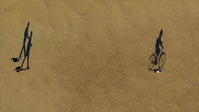 La sombra de la bici y del jinete se mueve lentamente en el parque Visión inusual desde el top almacen de video