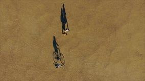 La sombra de la bici y del jinete se mueve lentamente en el parque Visión inusual desde el top metrajes