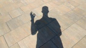 La sombra de las demostraciones de un hombre gesticula aceptable metrajes