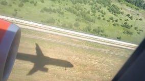 La sombra de un avión del vuelo en la tierra en un día soleado Visión desde la ventana del aeroplano Sombra del avión El volar en almacen de video