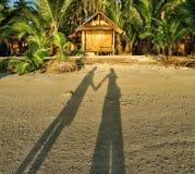 La sombra de un par en la puesta del sol vara cerca de la casa de planta baja Imágenes de archivo libres de regalías