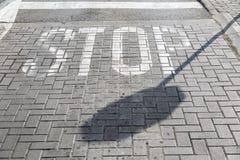 La sombra de una parada de la muestra contra la perspectiva de una calle pavimentada Fotos de archivo