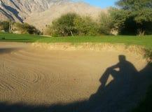 La sombra del hombre aparece ser que se sienta y de observación en trampa de arena del campo de golf fotos de archivo