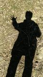 La sombra humana en las demostraciones de tierra cinco fingeres imagen de archivo libre de regalías