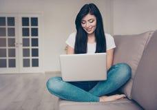 La sonrisa adolescente en casualwear se está sentando con las piernas cruzadas en el s Imagen de archivo
