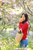 La sonrisa china asiática feliz de la muchacha de la belleza de la mujer en un campo de flor en una naranja de la fruta del olor  Fotografía de archivo