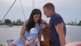 La sonrisa de hombres con la esposa y el niño en el lago, pareja casada agradable con el niño se relaja en el yate, el marido y e metrajes