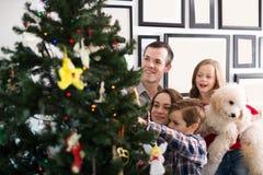 La sonrisa de los miembros de la familia adorna el árbol de navidad Fotos de archivo libres de regalías