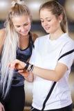 La sonrisa de mujeres mira estadísticas del entrenamiento sobre el reloj elegante de los deportes Fotografía de archivo libre de regalías