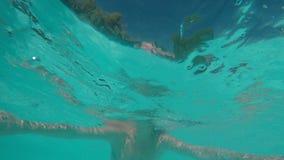 La sonrisa de tres amigos entra en la piscina y comienza a nadar metrajes