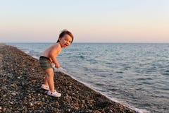 La sonrisa feliz 2 años de muchacho que se coloca en los guijarros vara en el sunse Fotos de archivo libres de regalías