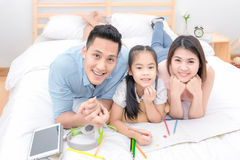 La sonrisa feliz de la familia asiática y se relaja en cama en casa Fotografía de archivo libre de regalías