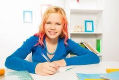 La sonrisa feliz de la muchacha, escribe en el libro de texto que hace la preparación Imagen de archivo libre de regalías