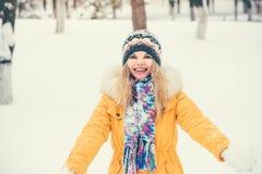 La sonrisa feliz del sombrero y de la bufanda de la mujer que lleva joven al aire libre disfruta de invierno Imagen de archivo