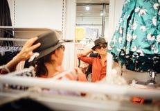 La sonrisa femenina intenta encendido la nueva mirada del sombrero en la reflexión de espejo imágenes de archivo libres de regalías