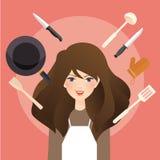 La sonrisa hermosa de la mujer alrededor de cocinar equipa los utensilios de la cocina que llevan el delantal Fotos de archivo libres de regalías