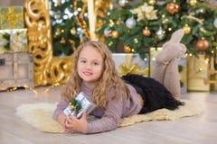 La sonrisa hermosa joven de la muchacha, sentándose cerca de abundancia de oro enorme del espejo presenta en las decoraciones de  Foto de archivo