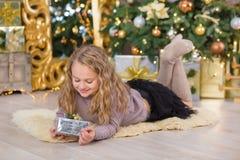 La sonrisa hermosa joven de la muchacha, sentándose cerca de abundancia de oro enorme del espejo presenta en las decoraciones de  Fotografía de archivo libre de regalías