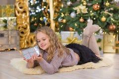 La sonrisa hermosa joven de la muchacha, sentándose cerca de abundancia de oro enorme del espejo presenta en las decoraciones de  Fotos de archivo