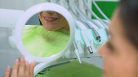 La sonrisa hermosa reflejó en el espejo, mujer satisfecha con el tratamiento de dientes almacen de video