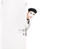 La sonrisa imita al artista que presenta detrás de una puerta de madera Imagenes de archivo