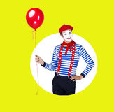 La sonrisa imita con el globo Actor divertido en boina roja Imagenes de archivo