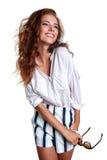 La sonrisa joven adelgaza a la hembra bronceada en pantalones cortos del dril de algodón que encoge su s Foto de archivo libre de regalías