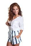 La sonrisa joven adelgaza a la hembra bronceada en pantalones cortos del dril de algodón que encoge su s Imagen de archivo libre de regalías