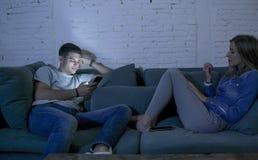 La sonrisa joven del sofá del sofá de los pares en casa feliz junto pero separado ignorándose concentró en el teléfono móvil en I imagenes de archivo