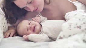 La sonrisa joven hermosa de la madre y besa a su niño recién nacido almacen de video