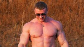 La sonrisa masculina hermosa del culturista del atleta y demuestra los músculos