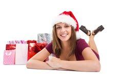 La sonrisa morena festiva en la cámara con el regalo empaqueta detrás de ella Imagen de archivo
