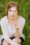 La sonrisa mujer bastante joven cubrió su ojo con el diente de león Imagen de archivo libre de regalías