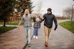 La sonrisa parents caminar abajo de la calle con un pequeño hijo en el A.C. Imagen de archivo libre de regalías