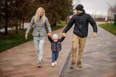 La sonrisa parents caminar abajo de la calle y divertirse con un li Fotografía de archivo libre de regalías